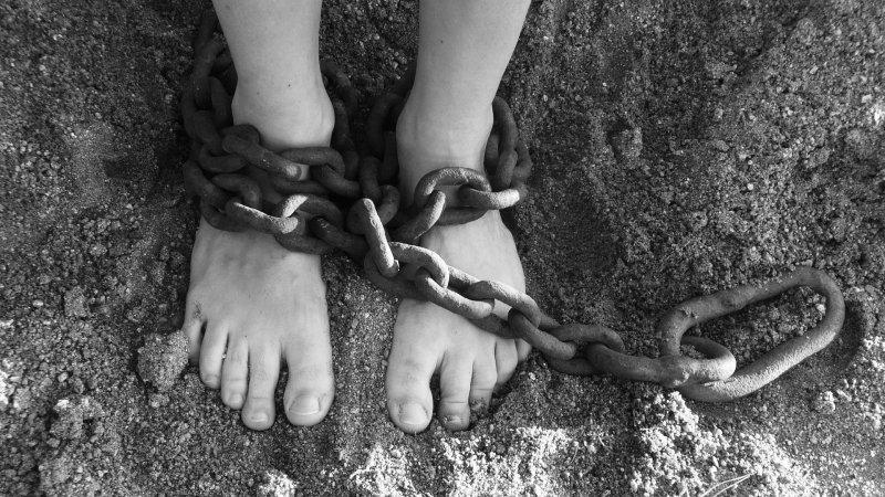 Vista cenital de pies infantiles encadenados.