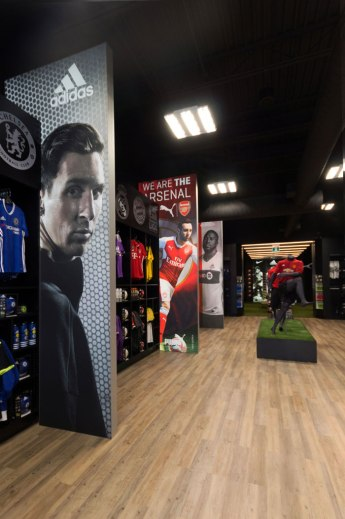 In2Sports Retail Store by Unfold Creative Studio - Custom lightbox graphics divide the space into zones pertaining to leagues, and creates a dynamic experience when you first walk into the store.