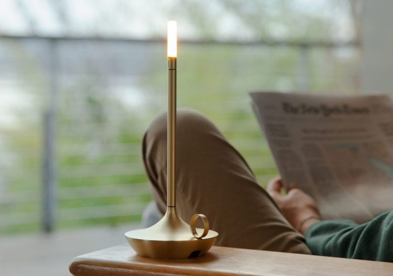 graypants, inc. wick brass portable candlelight on a side table with someone reading in the background