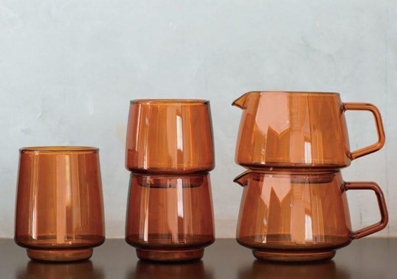 KINTO sepia glassware collection stacked in front of a dark grey background