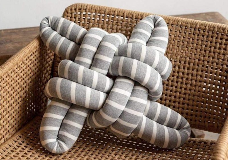 knots studio grey and white cotton knotted pillow on a chair
