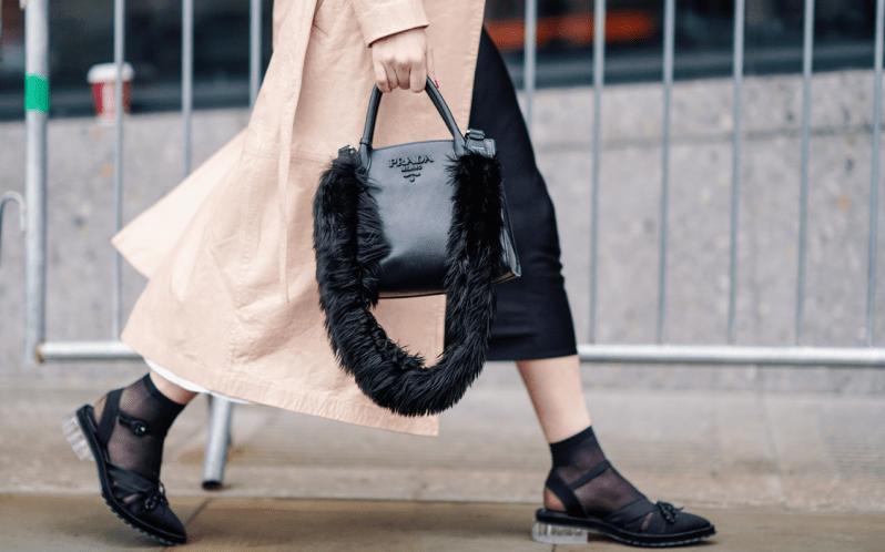 Žena v ponožkách v sandálech, dlouhém béžovém kabátě a s černou kabelkou Prada s kožešinovým popruhem v ruce.