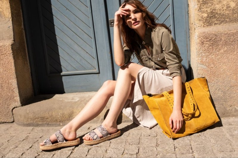 Žena v khaki košilových šatech sedící na zápraží starého domu u modrých dveří se semišovou kanárkově žlutou velkou kabelkou.