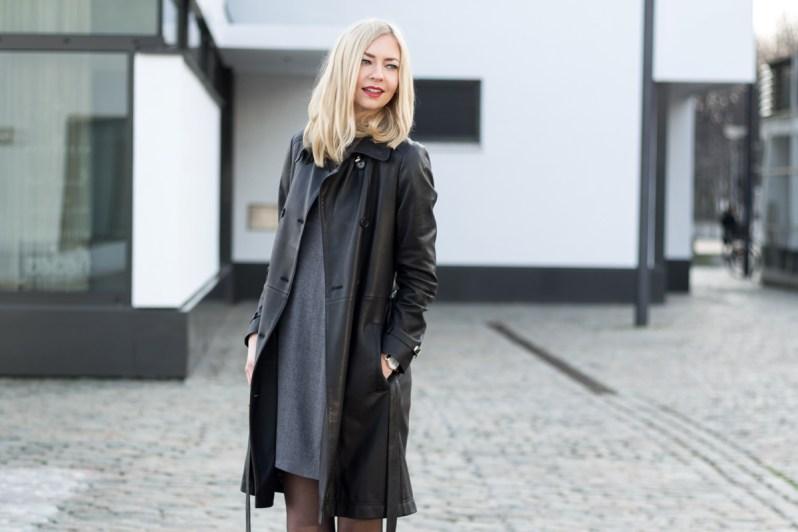 Blondýna v koženém kabátu a šedých mikinových šatech na ulici