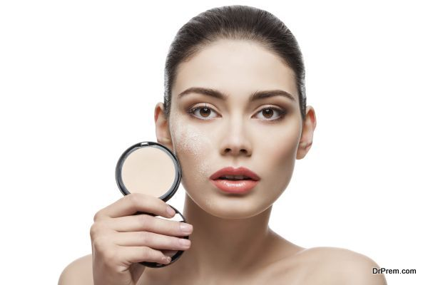 Beautiful young woman holding conrainer with pressed powder next to her face. Isolated over white background.