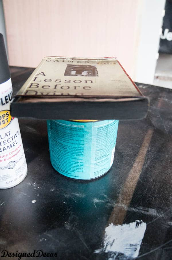 spray painting an old book to make a repurposed book flower