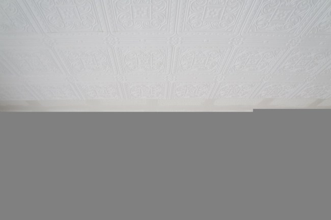 hanging wallpaper on ceiling to create faux tin tiles