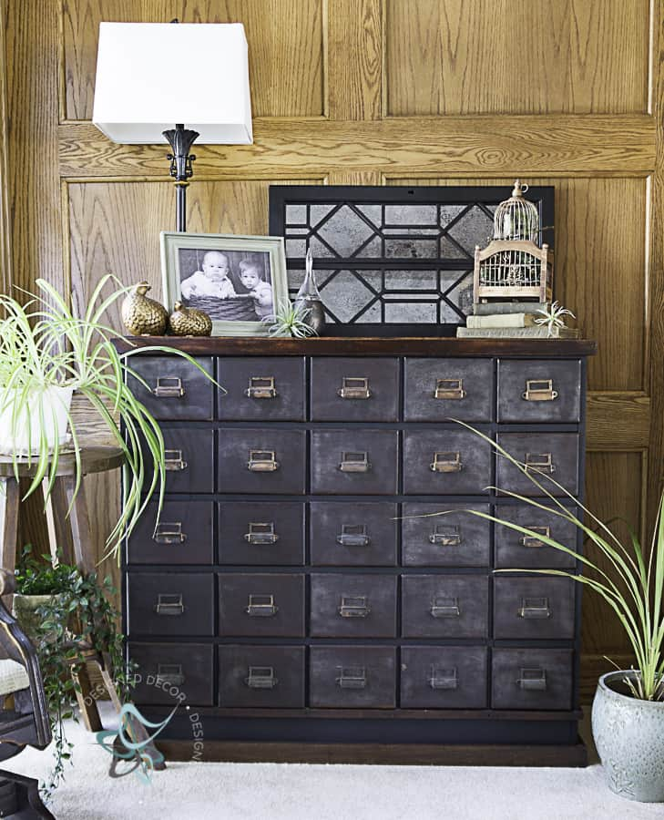 picture of an antique apothecary cabinet decorated with plants and home deocr accessories