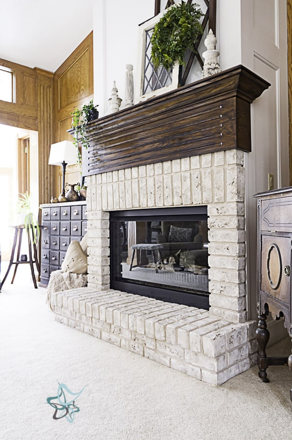 image of a decorated brick fireplace with a dark stained mantel and a white properly paint oak wall above the mantel