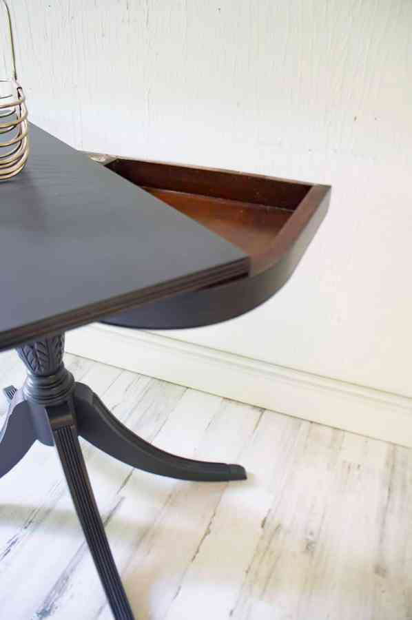 close up image of a half moon table with the top open to reveal the hidden compartment