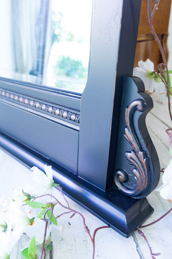 Close up image of a black painted mirror with light distressing on the carved details