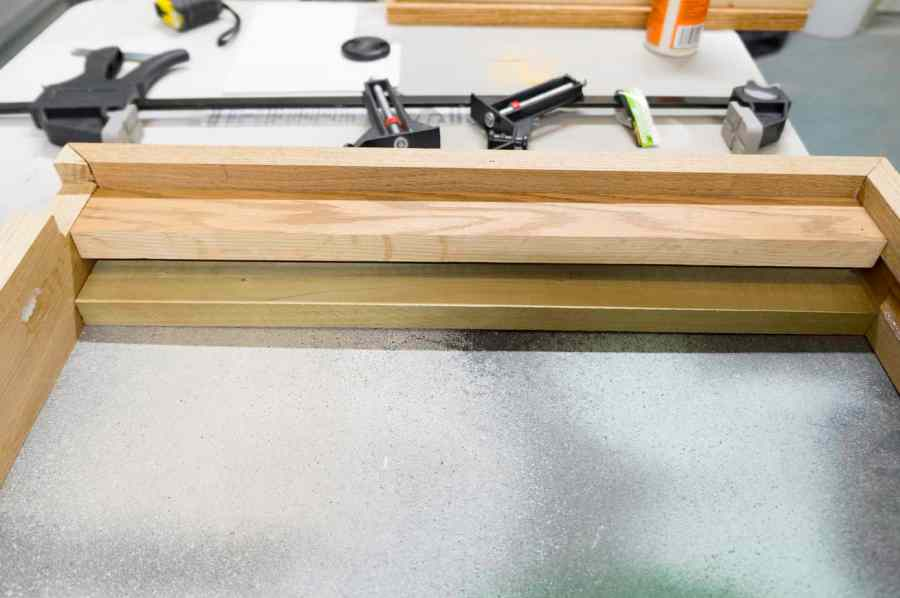 close up image of the wood support bar for the top of the jewelry cabinet frame