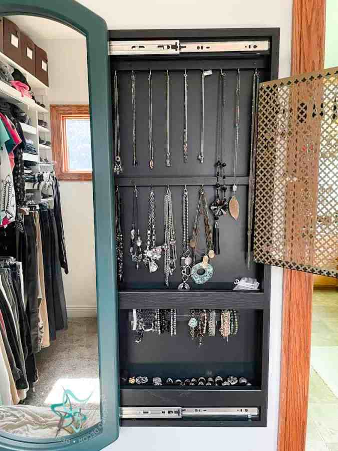 sliding mirror jewelry cabinet with mirror open and showing the hanging necklace area