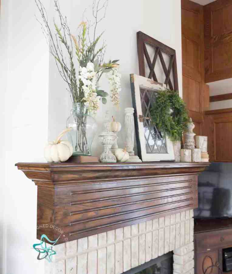 fireplace mantel with fall decor of windows, candlesticks, pumpkins and floral