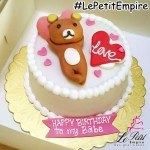 Customized White Fondant Cake with Bear Laying Down.