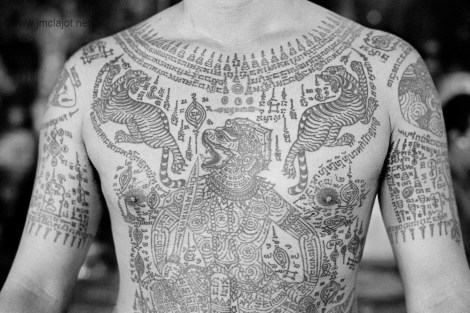 Arjan Noo Kanphai is a famous Thai tattoo artist. Tattooing mystic Buddhist warlock rock star is more like it. He is respected and venerated by masters, monks, movie stars (Angelina Jolie), gangsters, police, high and low society alike for his beautiful and powerful protective tattoos that are traditionally called Sak Yant. In Thailand, a country with a culture deeply rooted in spirituality and superstition, tattoos are a lot more than just skin deep. Traditional Thai tattoos, known as Yantra tattoos are believed to have strong magical powers.