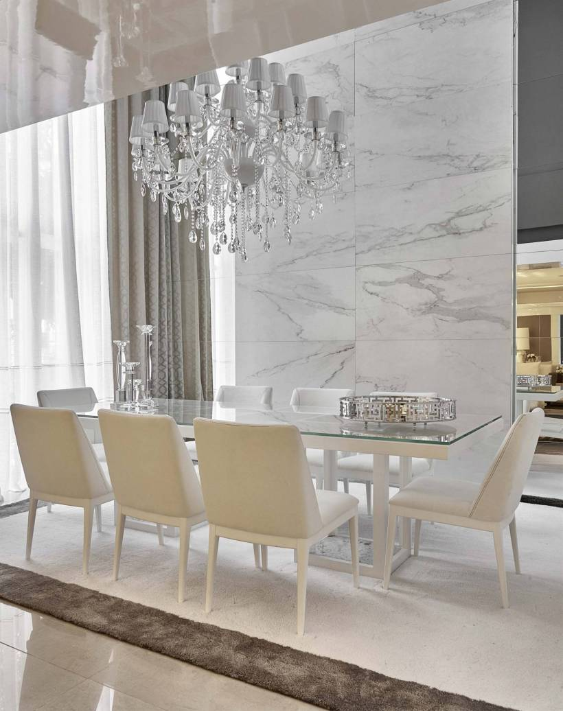 dining room with crystal chandelier, beige chairs and back wall of carerra marble
