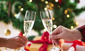 wine glasses being toasted by 2 people in front of christmas tree