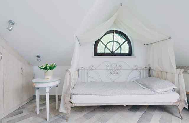Yatak üzerinde beyaz gölgelik perdeli tavan arası yatak odası