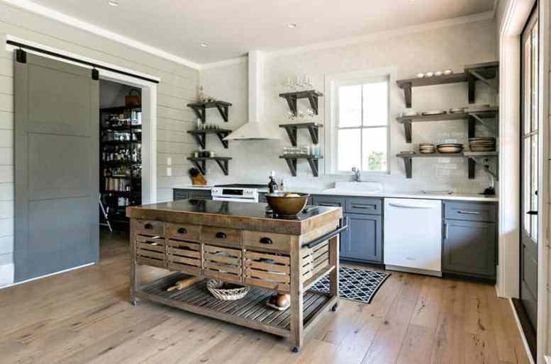 Rustieke keuken met open planken en houten tafel voor eiland