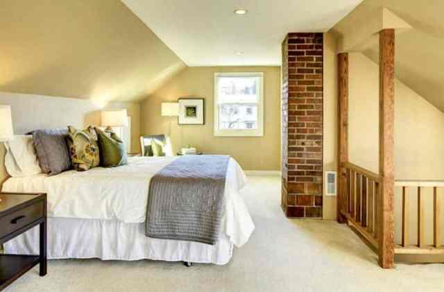 Çıplak tuğla şömine ve halı ile tavan arası yatak odası