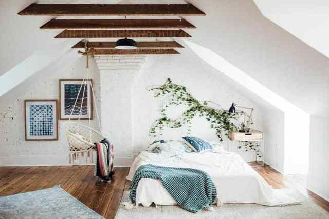 Eğimli duvarlara ve çıplak ahşap kirişlere sahip tavan arası yatak odası