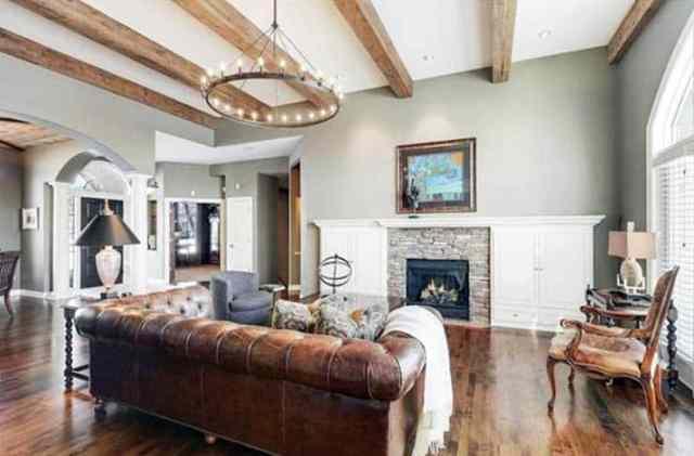Açık yeşil duvar boyası ve beyaz gömme dolaplı deri kanepe ile oturma odası