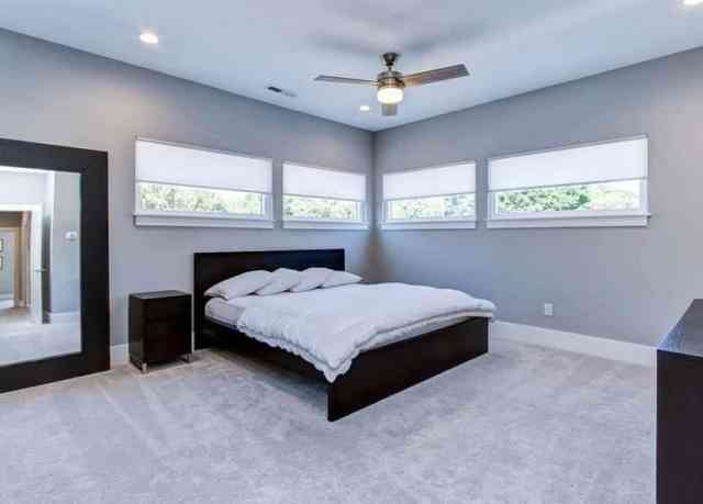 Pencere beyaz panjurların altına yatak yerleştirmeli modern yatak odası