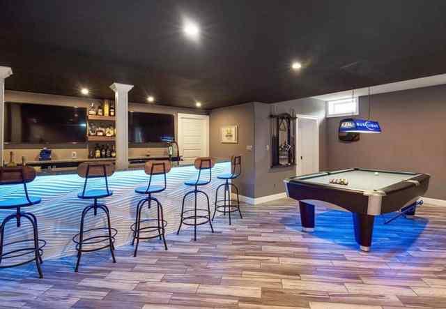Ev barı ve ahşap döşeme ile modern bodrum oyun odası