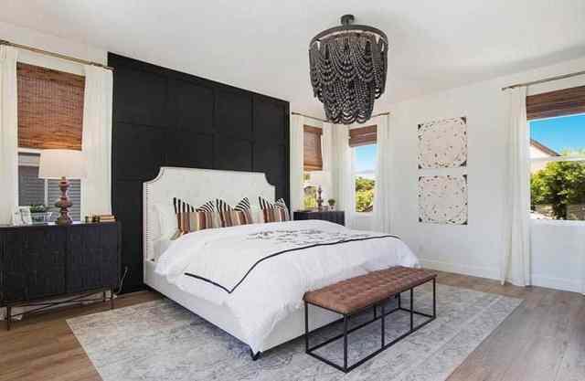 Yatak boncuklu asma avizenin arkasında siyah panelli vurgu duvarlı modern çiftlik evi yatak odası