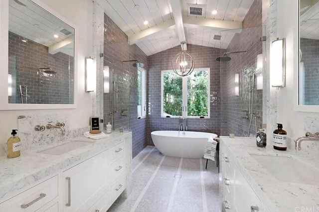 Ayaklı küvet ve ikili duş içeren güzel ana banyo