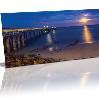 A beautiful sunset filled with blues and purples with the moon shinning it's beams over the water on the right and the lighted jetty on the left. The rocks and sand in the foreground