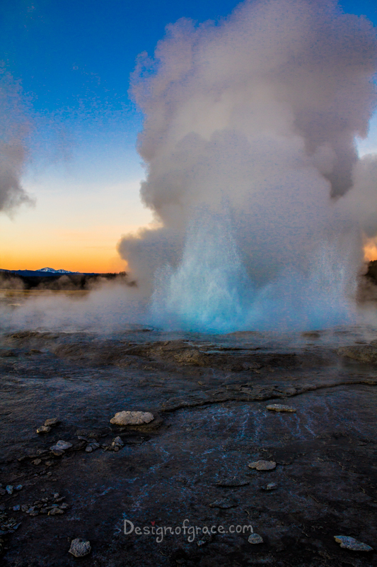 A beauitful orange and blue sunset with a mountain on the left. With the geyser erupting in the front with a blue core. The foreground is dark and rocky