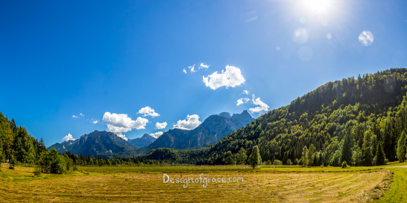 Bavarian Countryside with beautiful blue skies and lush green forest on mountains in the background and open fields in the foreground, Munich, Bavaria, Germany