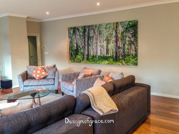 A photo of my client's living room with grey couch and orange and white pillows with the 3 x1.4m canvas print of the green and gray Karri Forest
