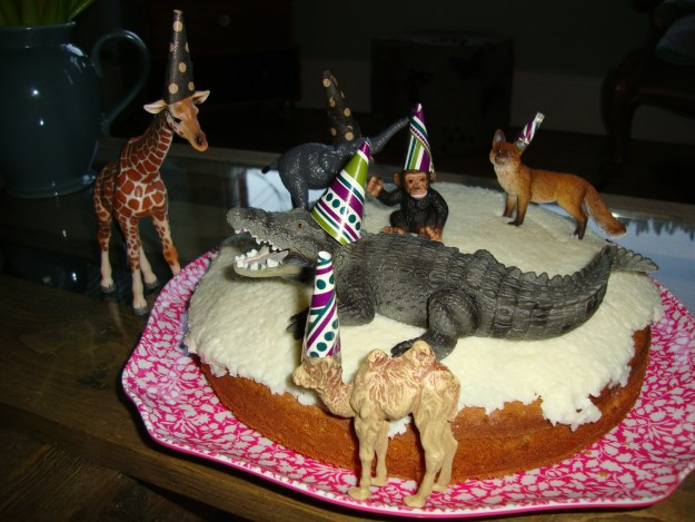 Pear and coconut celebration cake with schleich animal figurines in party hats