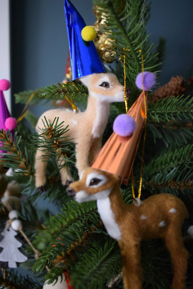 Christmas styling, miniature faux tree with bambi deer in party hats decorations