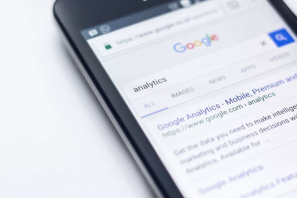 """A smartphone displaying Google's search engine results on """"analytics""""."""