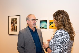 Carmon Colangelo, Dean of the Sam Fox School of Design & Visual Arts, talks with curator Susan Moore at the Stan Strembicki & Alumni Art Show Opening Reception, Des Lee Gallery, St. Louis, MO