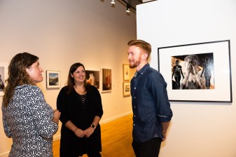 Curator Susan Moore talks with attendees at the Stan Strembicki & Alumni Art Show Opening Reception, Des Lee Gallery, St. Louis, MO