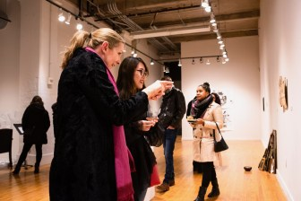 """Sixue Yang (right) talks with Patricia Olynyk, Director, Graduate School of Art, Sam Fox School of Design & Visual Arts, about her piece """"Fusing"""" at the Parabola: Assembly exhibition, Des Lee Gallery, Washington University, St. Louis, MO"""