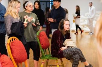 "Georgina Halpern (seated) views ""Informative Feed for HD"" by Madeline Halpern on display at the BFA Show 2, Des Lee Gallery, Washington University, St. Louis, MO"