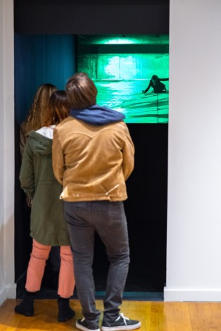 """Visitors watch """"Darkness"""" bu A;exa Velez on display at the Parabola: Extraterrestrial Exhibit Opening, Des Lee Gallery, Washington University, St. Louis, MO"""