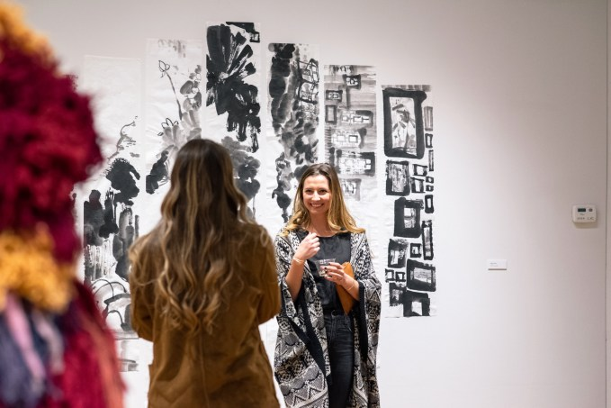 """Liz Moore (back to camera) and Ellen Ward in front of """"Ink on Xuan paper"""" by Sixue Yang on display at the Parabola: Extraterrestrial Exhibit, Des Lee Gallery, Washington University, St. Louis, MO"""