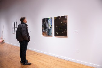 """Steve Knight views """"OOPS! I Dropped My Cellphone!"""" by Adrian Gonzalez on display at the Parabola: Extraterrestrial Exhibit, Des Lee Gallery, Washington University, St. Louis, MO"""