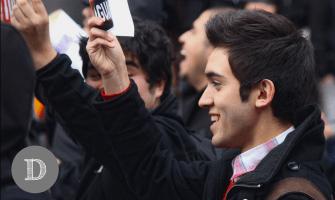 Chaqueta negra tipo montgomery, camisa cuadrillé y chaleco rojo.