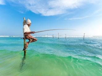 Elderly stilt fisherman at Hikkaduwa Beach.