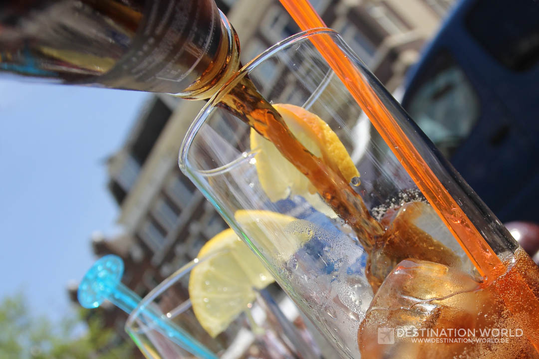 Cola in ein Glas mit Eiswürfeln gießen
