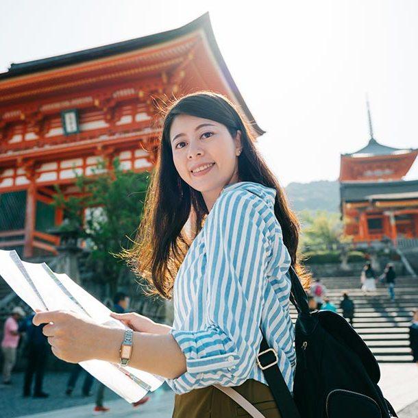 Femme tenant une carte devant un sanctuaire au Japon