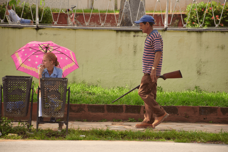 A farmer walks through Vinales with a rifle while a lady waits for the bus